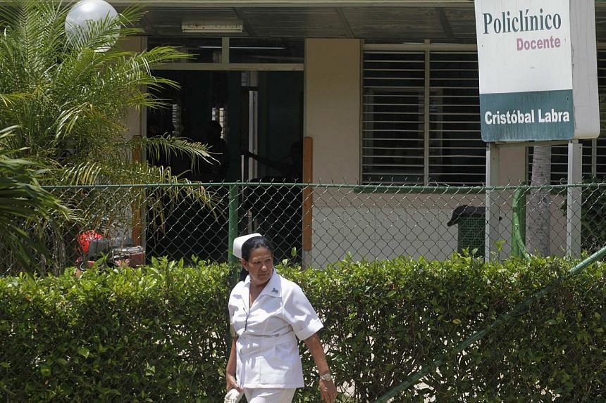 A nurse walks outside the Cristobal Labra health clinic, where according to local media, victims of an alcohol poisoning incident were first treated before being transferred to a hospital, in Havana on July 31, 2013. -- FILE PHOTO: REUTERS