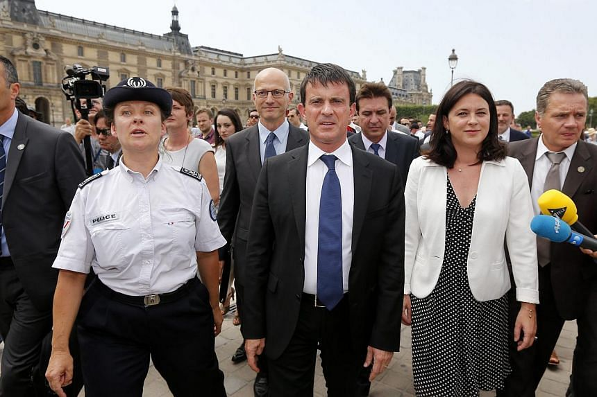 French Interior Minister Manuel Valls (centre) and Junior Minister of Crafts, Business and Tourism Sylvia Pinel (third, right) are surrounded by journalists as they walk with a police woman outside the Louvre museum in Paris on Aug 2, 2013 during a t