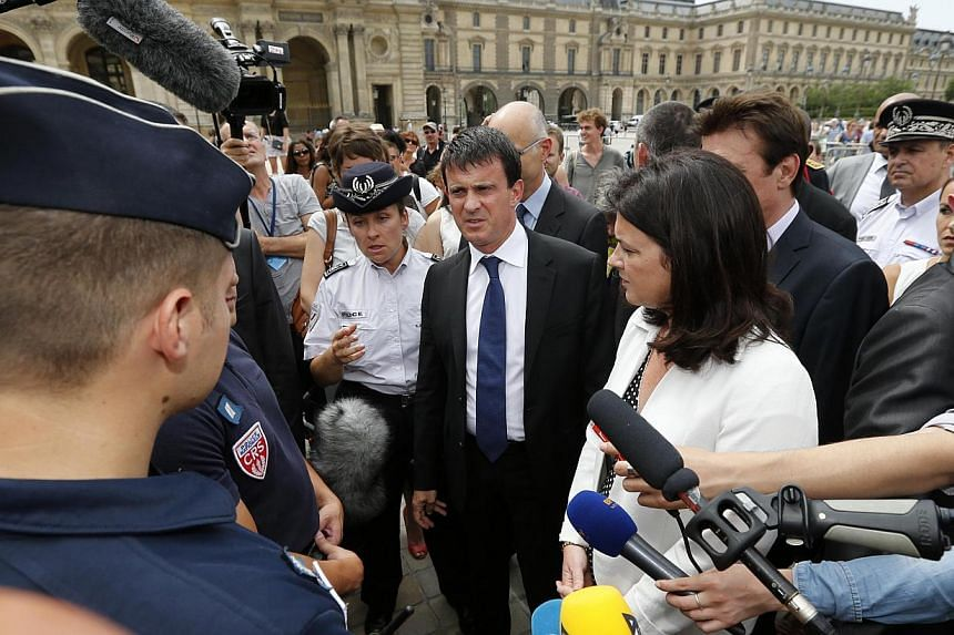 French Interior Minister Manuel Valls (centre) and Junior Minister of Crafts, Business and Tourism Sylvia Pinel (second, right) speak with French CRS police surrounded by journalists outside the Louvre museum in Paris on Aug 2, 2013 during a tour foc