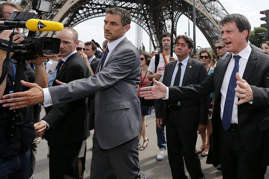 French Interior Minister Manuel Valls (right) gestures as he walks surrounded by journalists next to the Eiffel Tower in Paris on Aug 2, 2013 during a tour focused on security at the city's top tourist areas. -- PHOTO: REUTERS
