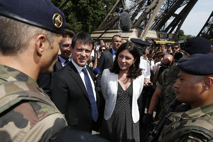French Interior Minister Manuel Valls (second, left) and Junior Minister of Crafts, Business and Tourism Sylvia Pinel (centre) speaks with French soldiers patrolling near the Eiffel Tower in Paris on Aug 2, 2013 during a tour focused on security at t