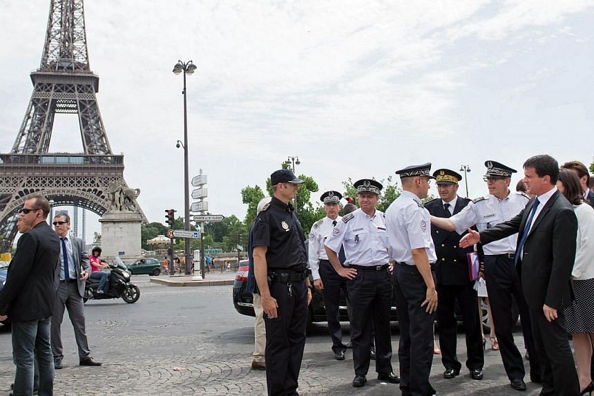 French Interior Minister Manuel Valls (second, right) and French Junior Minister for Handicraft, Tourism and Trade Sylvia Pinel (right) verify security measures taken to protect tourists around the Eiffel Tower area on Aug 2, 2013 in Paris.&nbs