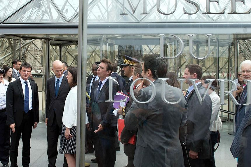 French Interior Minister Manuel Valls (second, left) and French Junior Minister for Handicraft, Tourism and Trade Sylvia Pinel (fourth, left) verify security measures taken to protect tourists around the Louvre Museum area on Aug 2, 2013 in Paris. --