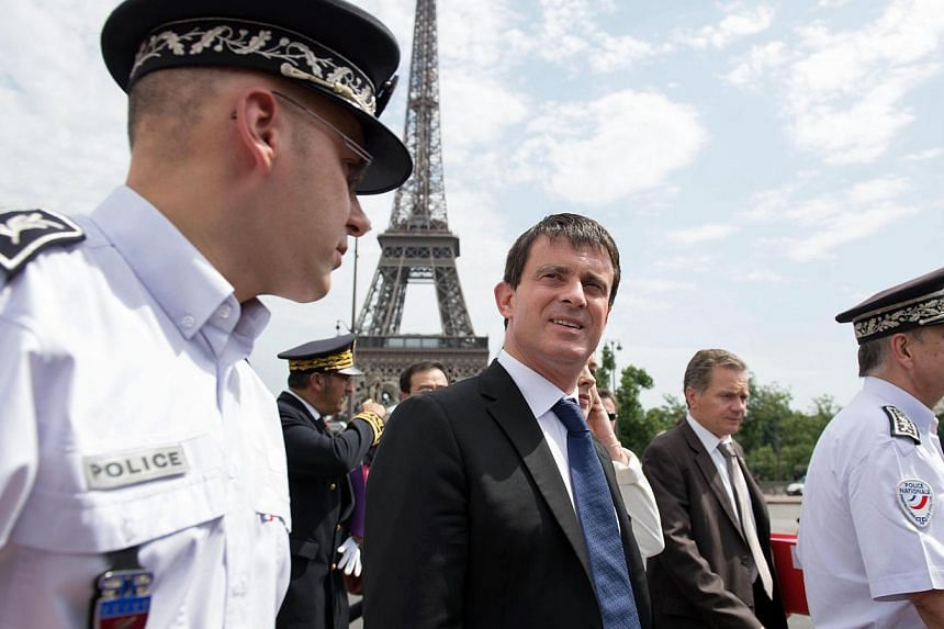 French Interior Minister Manuel Valls (centre) and French Junior Minister for Handicraft, Tourism and Trade Sylvia Pinel (unseen) verify security measures taken to protect tourists around the Eiffel Tower area on Aug 2, 2013 in Paris. -- PHOTO: AFP