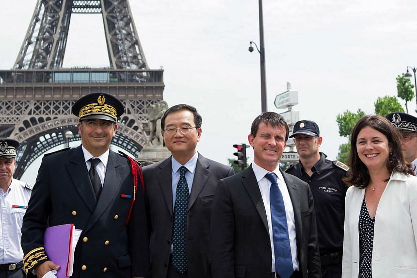 French Interior Minister Manuel Valls (second, right) and French Junior Minister for Handicraft, Tourism and Trade Sylvia Pinel (right) verify security measures taken to protect tourists around the Eiffel Tower area on Aug 2, 2013 in Paris. -- PHOTO: