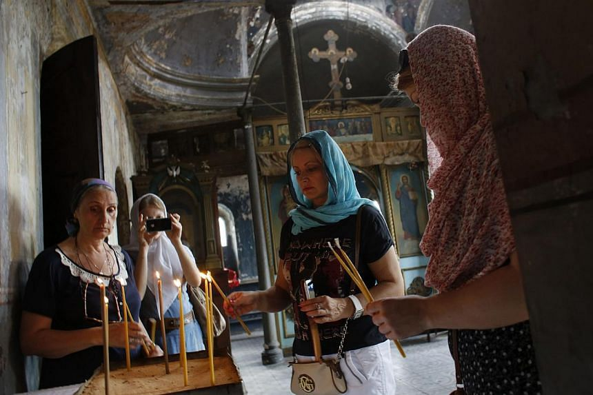 Russian Orthodox worshippers light candles at St. Elijah Church in Istanbul on Aug 2, 2013.About 25 Russian Orthodox celebrated a divine liturgy on Friday for the first time in four decades at their rooftop church they fear may be demolished to