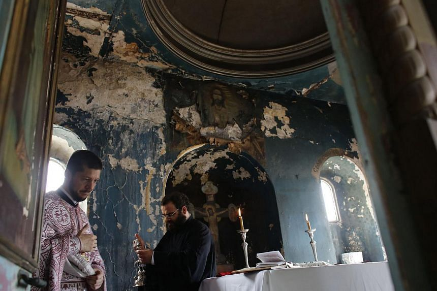 Greek Orthodox priest Visarion of the Ecumenical Greek Orthodox Patriarchate (left) leads a service at the Russian Orthodox St. Elijah Church in Istanbul on Aug 2, 2013. -- PHOTO: REUTERS