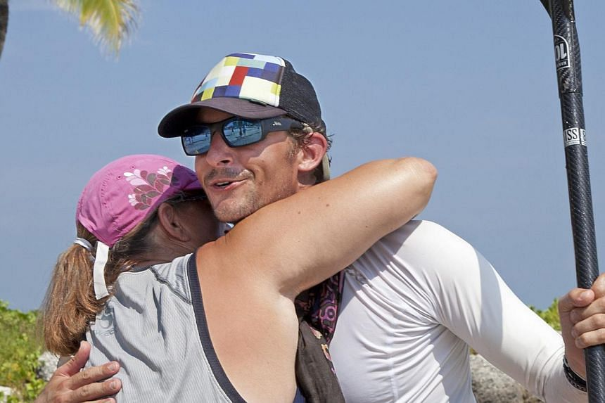 In this photo provided by the Florida Keys News Bureau, Mr Ben Friberg, right, is hugged by Ms Ruth Holland after arriving in Key West, Florida, on Friday, Aug 2, 2013, following a 177km voyage from Cuba across the Florida Straits to the Florida Keys