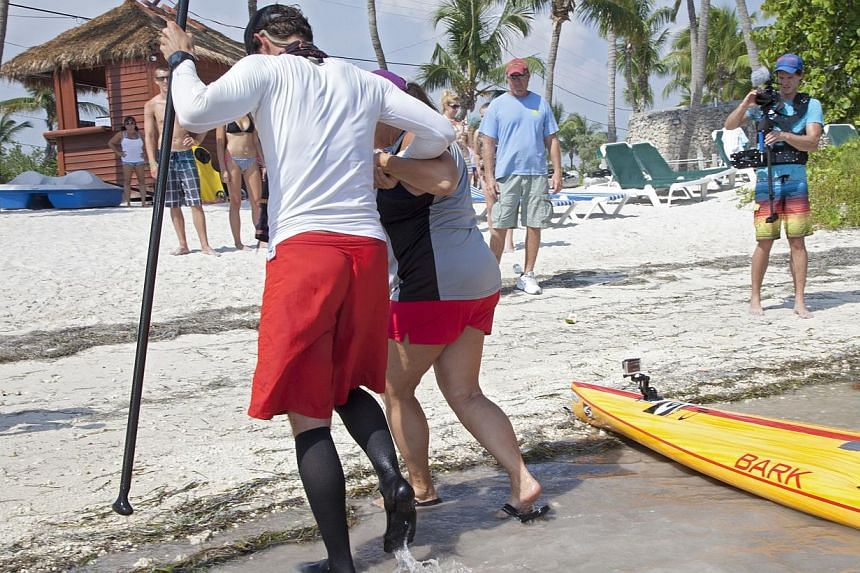 In this photo provided by the Florida Keys News Bureau, Mr Ben Friberg, left, is helped to shore by Ms Ruth Holland after arriving in Key West, Florida, on Friday, Aug 2, 2013, following an 177km voyage from Cuba across the Florida Straits to the Flo