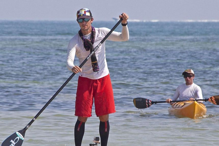 Mr Ben Friberg (left) paddles the last few yards to arrive in Key West, Florida, after completing a 177km paddleboarding from Cuba across the Florida Straits to the Florida Keys on Aug 2, 2013. -- PHOTO: REUTERS