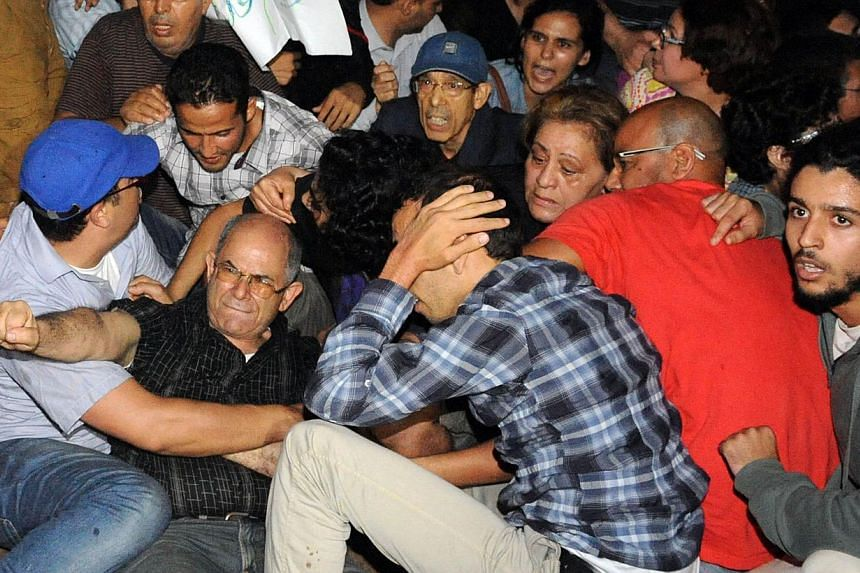 Angry protesters stage a demonstration on Aug 2, 2013, in Rabat-Morocco to protest the release of a Spanish paedophile, Daniel Fino Galvan, who raped 11 local children was pardoned by the Moroccan King Mohammed VI. -- PHOTO: AFP