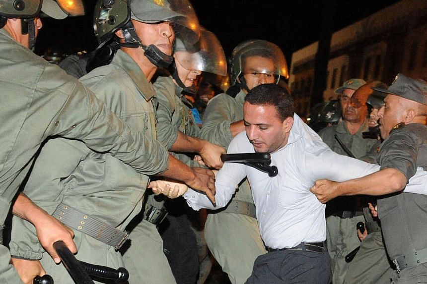 Policemen arrest a protester during a demonstration on Aug 2, 2013, in Rabat-Morocco on the release of a Spanish paedophile, Daniel Fino Galvan, who raped 11 local children was pardoned by the Moroccan King Mohammed VI. -- PHOTO: AFP