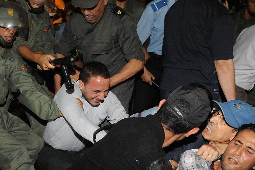Policemen arrest protesters during a demonstration on Aug 2, 2013, in Rabat-Morocco on the release of a Spanish paedophile, Daniel Fino Galvan, who raped 11 local children was pardoned by the Moroccan King Mohammed VI.  -- PHOTO: AFP