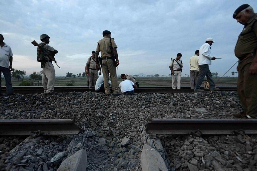 Indian bomb squad personnel and security officials survey damage to rails as they search railway tracks on the outskirts of Bodh Gaya, following an explosion which halted train traffic near the city in the eastern state of Bihar on Saturday, Aug 3, 2