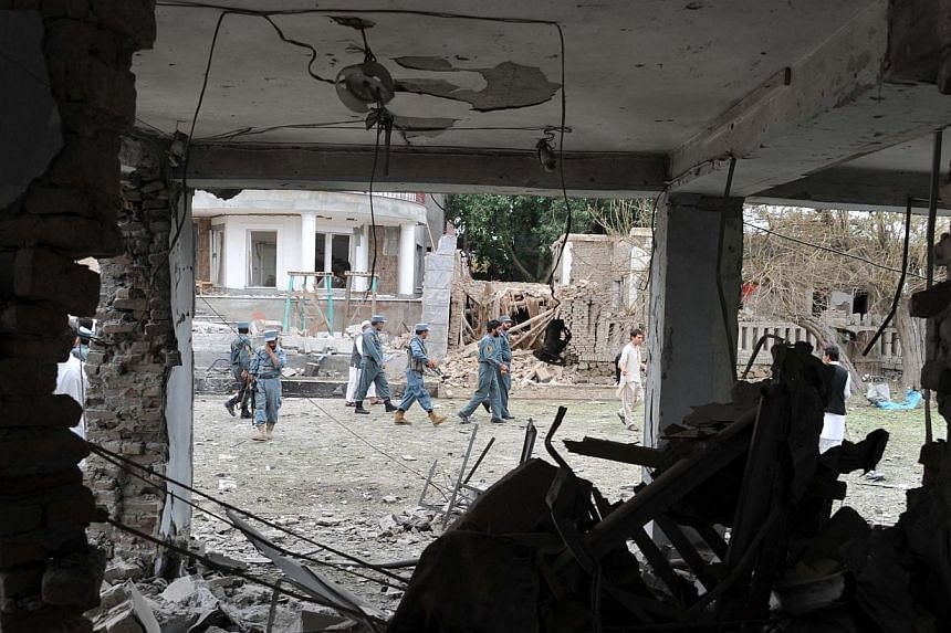 Afghanistan policemen walk at the site of a suicide attack in front of the Indian consulate in Jalalabad on Saturday, Aug 3, 2013. Suicide bombers targeted the Indian consulate in the eastern Afghan city of Jalalabad on Saturday, detonating an explos