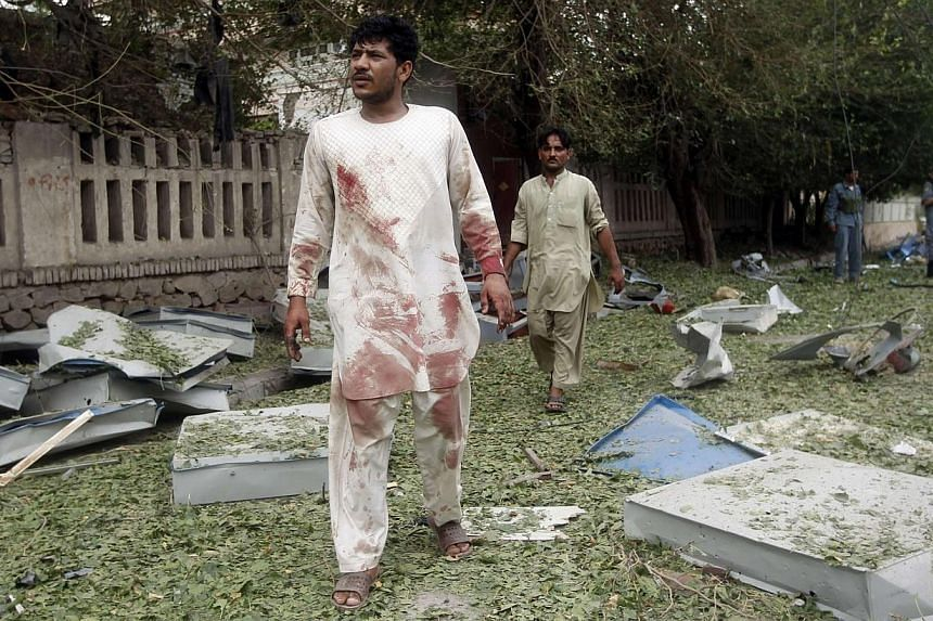 Men walk at the site of a suicide attack in Jalalabad province on Saturday, Aug 3, 2013. Suicide bombers targeted the Indian consulate in the eastern Afghan city of Jalalabad on Saturday, detonating an explosives-packed car outside the building and k
