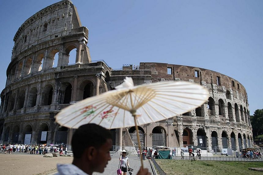 A vendor holds up a Chinese paper umbrella on a hot summer day in front of Rome's ancient Colosseum on Sunday, July 28, 2013. -- FILE PHOTO: REUTERS