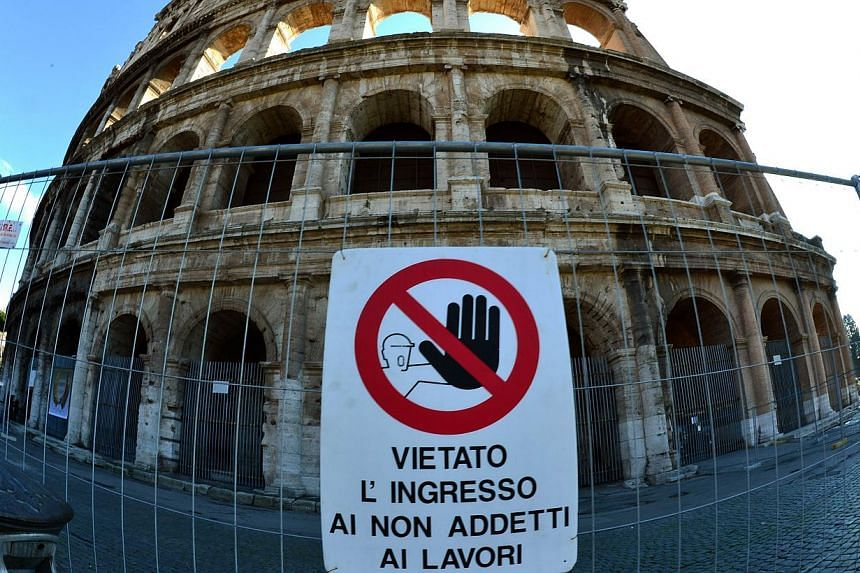 """A placard reading """"No entrance during works"""" hangs in front of the Colosseum in Rome on Jan 18, 2013. The city of Rome has from Saturday, Aug 3, 2013, barred private vehicles from using the main road to the Colosseum in order to protect the iconic mo"""