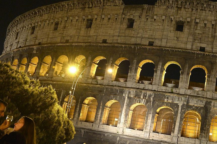 A couple chats outside the Colosseum in Rome on Thursday, May 2, 2013. -- FILE PHOTO: AFP