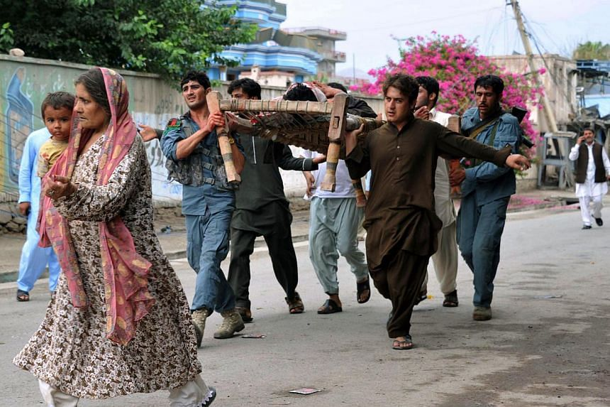 Afghan volunteers and security personnel carry a wounded man at the site of a suicide attack in front of the Indian consulate in Jalalabad on August 3, 2013. Suicide bombers targeted the Indian consulate in the eastern Afghan city of Jalalabad, killi