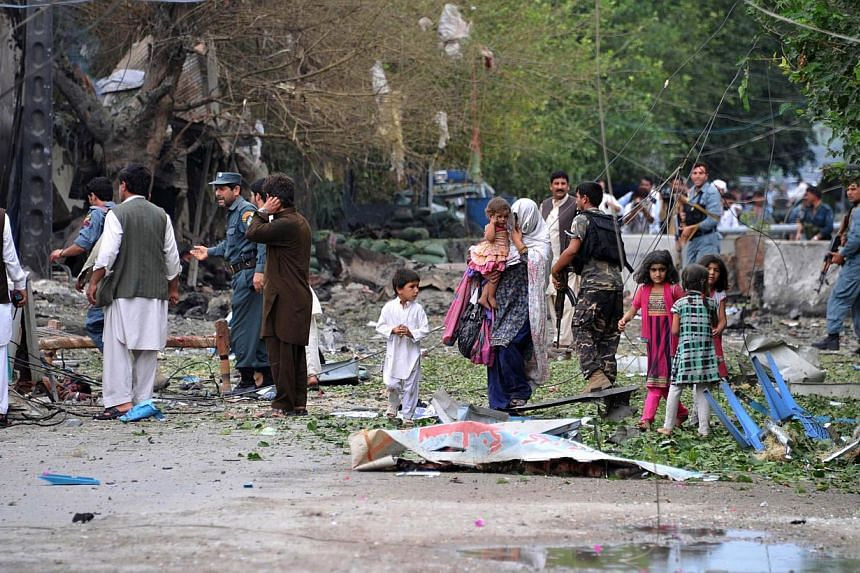 Afghanistan policemen and civilians walk at the site of a suicide attack in front of the Indian consulate in Jalalabad on August 3, 2013. Suicide bombers targeted the Indian consulate in the eastern Afghan city of Jalalabad, killing at least nine civ