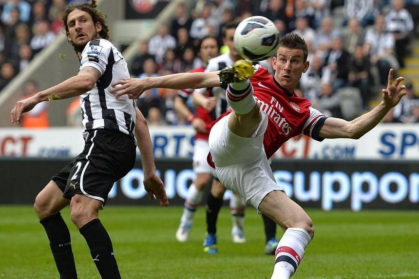 Arsenal's Lourent Koscielny (right) scores against Newcastle United during their English Premier League (EPL) soccer match at St James' Park in Newcastle, northern England, on May 19, 2013. StarHub will shave $300 off the bills of football fans who c