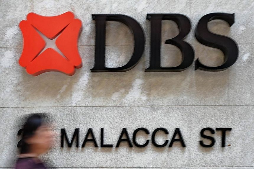 "A person walks past Development Bank of Singapore (DBS) signage in the financial district of Singapore on Feb 9, 2012. The collapse of Singapore lender DBS's US$6.5 billion (S$8.3 billion) bid for Bank Danamon is further evidence of a ""rising tide of"