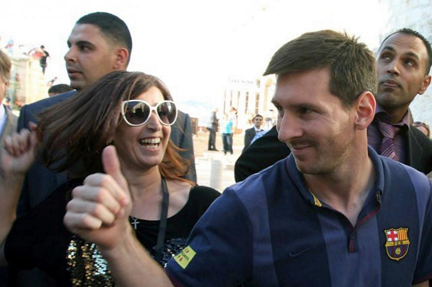 FC Barcelona forward Lionel Messi (centre) gives the thumbs up as he walks in Manger Square in the West Bank Biblical town of Bethlehem on Aug 3, 2013. Israeli President Shimon Peres on Sunday, Aug 4, 2013, praised Lionel Messi and his fellow B