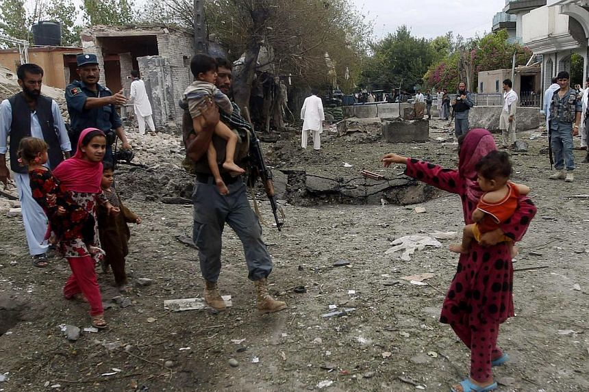 Afghan policemen carry children at the site of a suicide attack at the Indian consulate in Jalalabad province August 3, 2013.Suicide bombers targeted the Indian consulate in the eastern Afghan city of Jalalabad on Saturday, detonating an explos