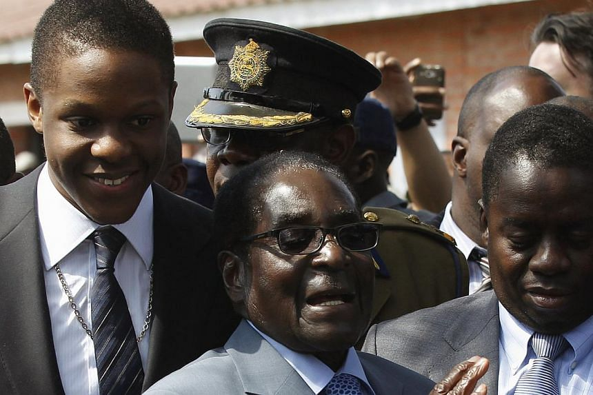 """Zimbabwean President Robert Mugabe reacts as he leaves after casting his vote in Highfields, outside Harare July 31, 2013. The United States on Saturday said results indicating a landslide victory for Zimbabwe's Robert Mugabe were not """"credible"""" and"""