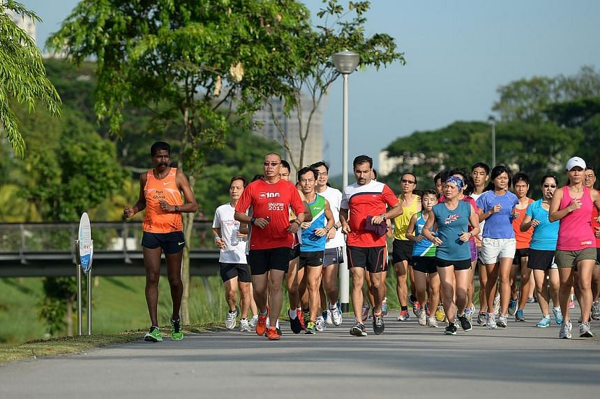 Participants in The Straits Times Run in the Park clinic doing the 3km run with national head coach for middle and distance running Ghana Segaran. -- ST PHOTO: JAMIE KOH