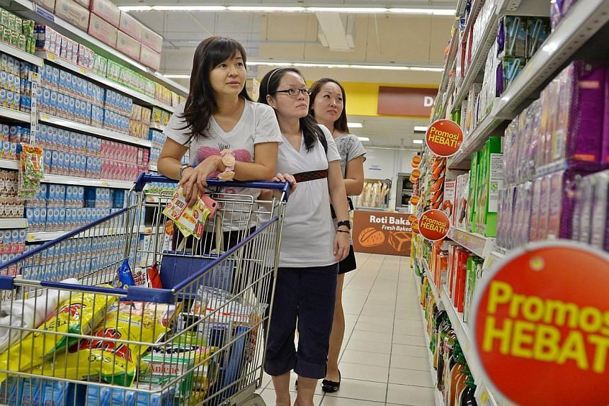(Above, from left) Madam Irene Yeo, Ms Serene Ang and Mrs Cassandra Lim buying groceries at Tesco in Johor Baru's KSL City last Thursday. Besides shopping, taking a trip to Johor Baru is like a gathering for the three friends. -- ST PHOTOS: RAJ NADAR