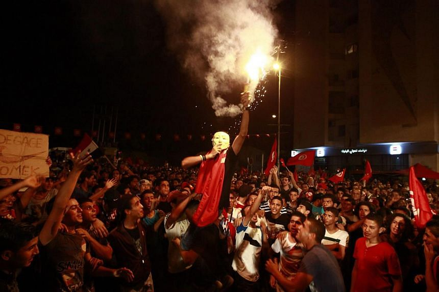 """A demonstrator holds up a flare during a protest to demand the ouster of the Islamist dominated government, outside the Constituent Assembly headquarters in Tunis on Sunday, August 4, 2013. Tunisia said its forces killed a """"terror"""" suspect in a dawn"""