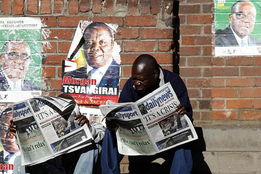 "Locals read newspapers in Mbare township, outside Harare on Sunday, Aug 4, 2013. Robert Mugabe looked on Sunday to a seventh term as Zimbabwe's president after winning elections denounced by the opposition as ""stolen"" and criticised by Western powers"