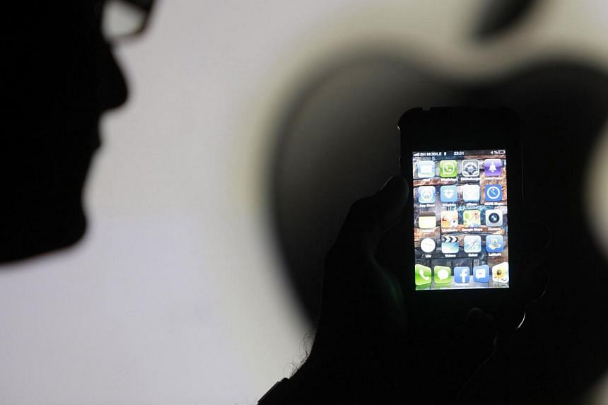 A man is silhouetted against a video screen with the Apple logo as he poses with an Apple iPhone 4 smartphone. The United States took the rare step on Saturday of vetoing a trade panel's decision to ban the sale of some Apple products, dealing a blow