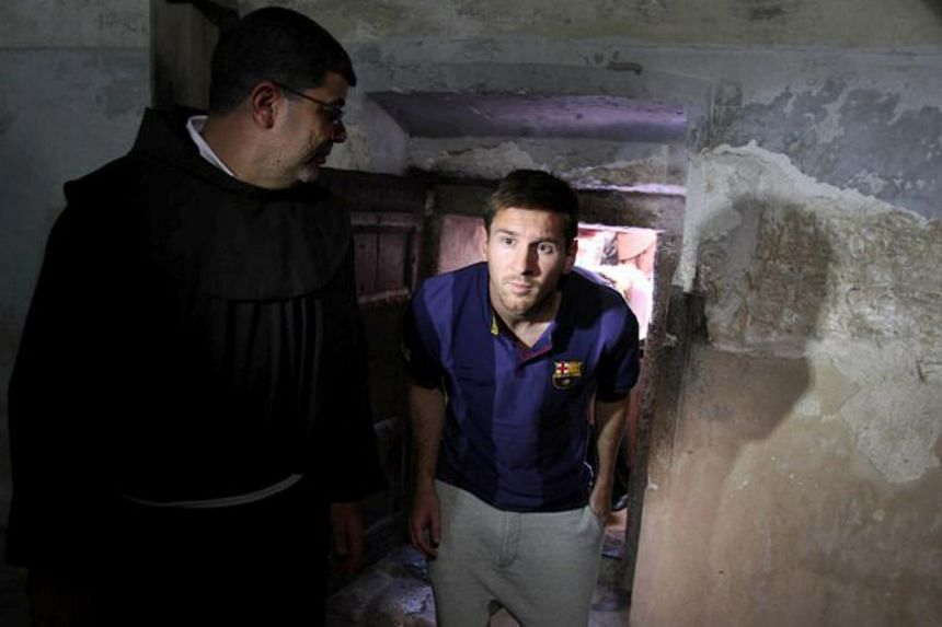 FC Barcelona forward Lionel Messi (centre) visits the Church of the Nativity in the West Bank Biblical town of Bethlehem on Aug 3, 2013.Israeli President Shimon Peres on Sunday, Aug 4, 2013, praised Lionel Messi and his fellow Barcelona s