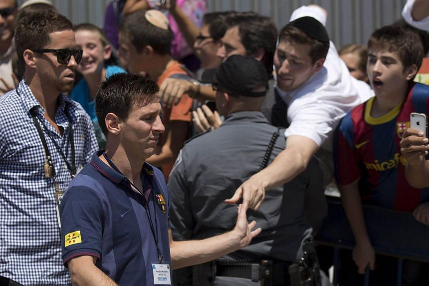 Barcelona's football player, Lionel Messi is greeted by Israelis during a visit by the team to the Western Wall in the Jerusalem old city on Sunday, Aug 4, 2013.Israeli President Shimon Peres on Sunday praised Lionel Messi and his fellow Barcel