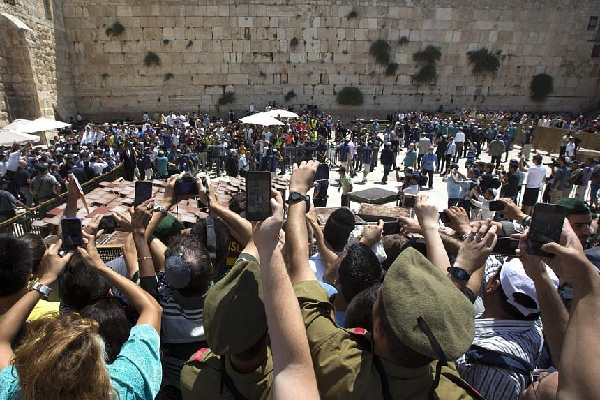 Israelis flock at the plaza in front of the Western Wall as they try to take pictures during a visit of Lionel Messi and his fellow Barcelona FC stars in the Jerusalem old city on Sunday, Aug 4, 2013.Israeli President Shimon Peres on Sunday pra