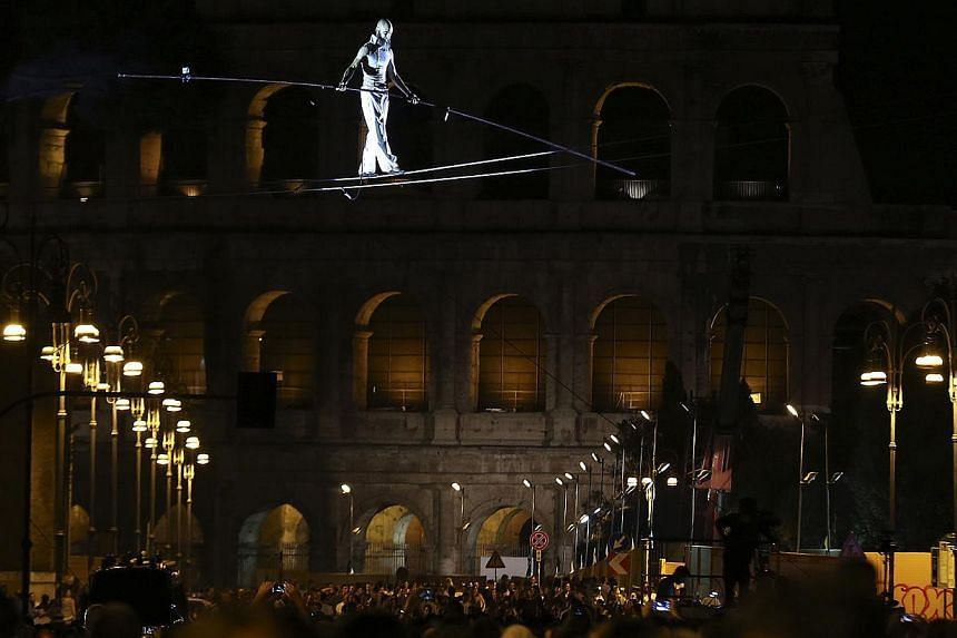 Tightrope walker Andrea Loreni performs in front of the Colosseum in Rome in the night of Aug 3, 2013. The city of Rome kicked off an all-night street party on Saturday to celebrate the blocking of the main road to the Colosseum to private vehicles t