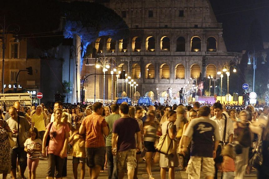 People gather the Fori Imperiali avenue, with the Colosseum in background, during an event celebrating the ban to private vehicles, in Rome, Saturday, Aug 3, 2013. Rome has begun a traffic ban to protect ancient glories from modern perils, allowing o