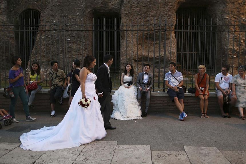 Newlyweds visit Fori Imperiali street before a ceremony to inaugurate a scheme that bans private vehicles on it, in Rome Aug 3, 2013. -- PHOTO: REUTERS