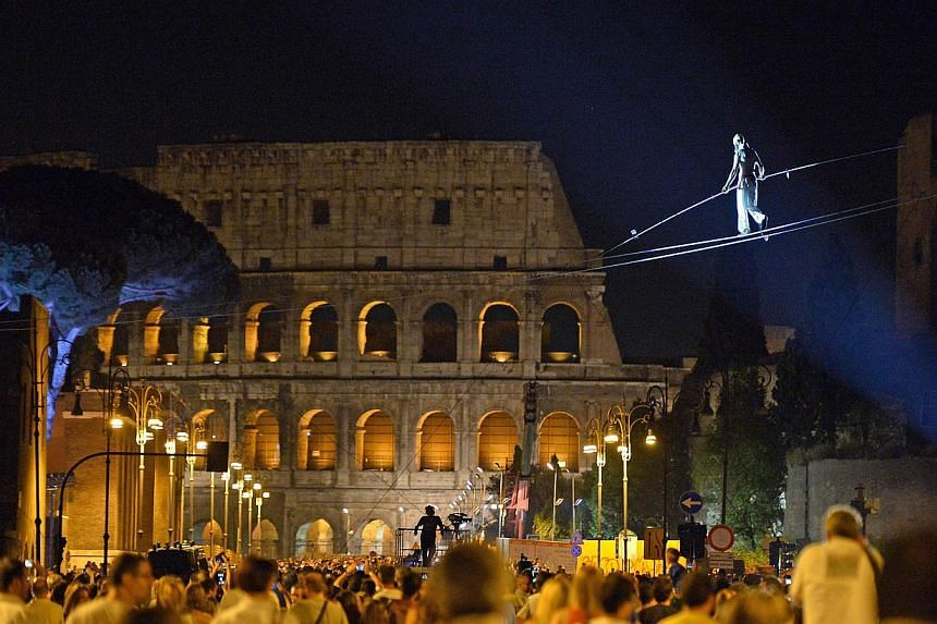 Tightrope walker Andrea Loreni performs in front of the Colosseum in Rome in the night of August 3, 2013. The city of Rome kicked off an all-night street party on Saturday to celebrate the blocking of the main road to the Colosseum to private vehicle