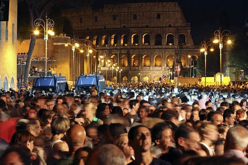 People visit Fori Imperiali street before the ceremony to inaugurate a scheme that bans private vehicles on it, in Rome August 3, 2013. The city of Rome kicked off an all-night street party on Saturday to celebrate the blocking of the main road to th