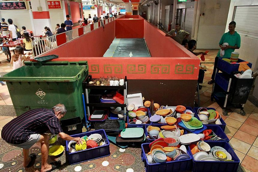 A stall owner picking up his used plates from outside the centralised washing area at Albert Food Centre. Hawker centres could soon join restaurants and food courts in outsourcing the washing of their plates and bowls. -- TNP FILE PHOTO: GAVIN FOO
