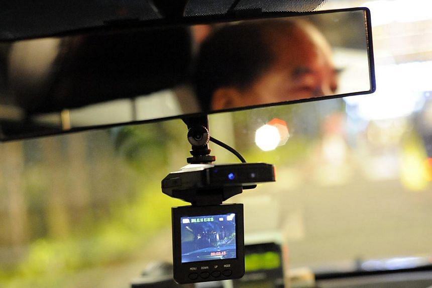 Comfort Taxi relief cabby Mr Roy Lee displays his in-vehicle camera. The next time your in-car surveillance camera captures a speeding motorist on the roads, don't just upload it online. Send it to the Traffic Police, too. -- ST FILE PHOTO: MARK CHEO