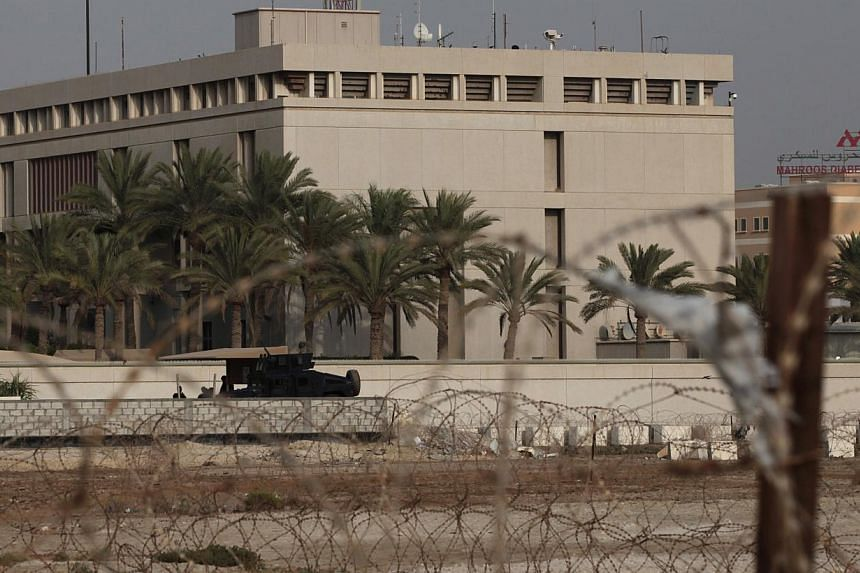 A Bahraini armored personnel vehicle and personnel reinforce U.S. Embassy security just outside of a gate to the building, surrounded in barbed wire, in Manama, Bahrain, on Sunday, Aug. 4, 2013. The United States said on Sunday that 19 of its em