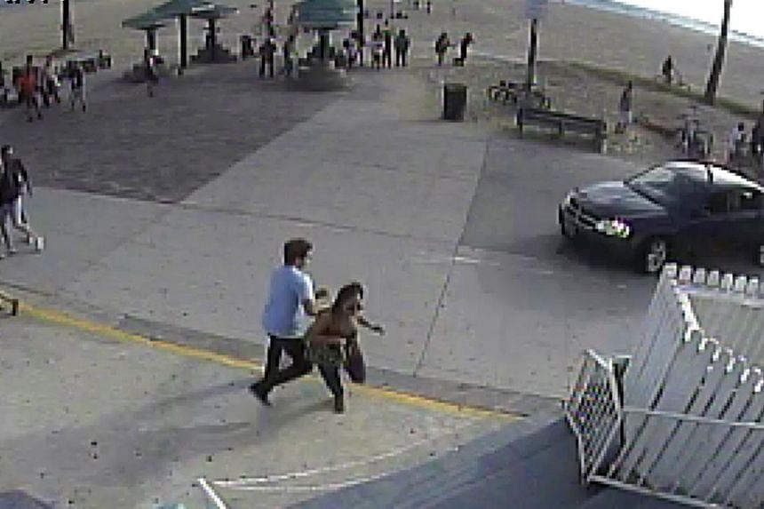 In this still frame made from security camera footage from Snapchat, Inc. headquarters, pedestrians scatter as a car drives through a packed afternoon crowd along the Venice Beach boardwalk in Los Angeles, Saturday, Aug. 3, 2013.A 38-year-old m