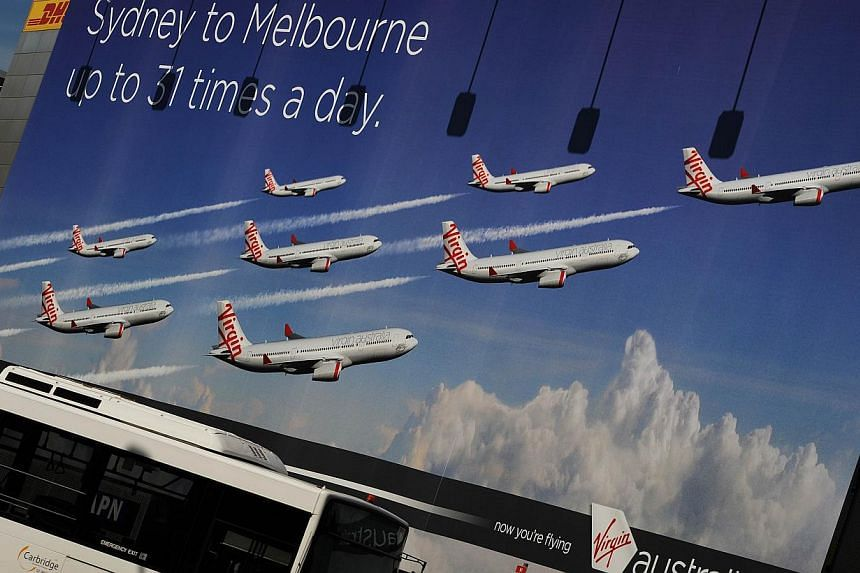 This photo taken on Aug 28, 2012 shows a bus (below) driving past a Virgin Australia Airline billboard displayed at the entrance to Sydney Airport. Virgin Australia said on Aug 5, 2013 that it was expecting a full-year loss of US$84 to US$98 million