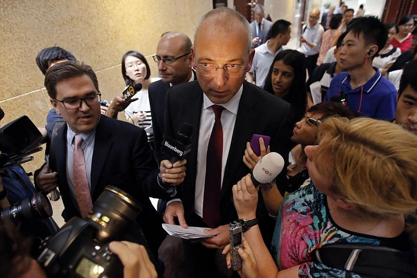 Fonterra Chief Executive Theo Spierings (centre) is surrounded by journalists as he leaves after a news conference in Beijing Aug 5, 2013. New Zealand's Fonterra said on Monday that milk products from two companies that use its raw materials are safe