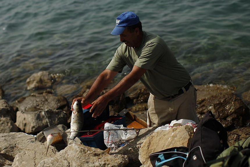 """A man fishes at a beach in Gibraltar, south of Spain on Aug 4, 2013. Gibraltar has sharply criticised a threat by Spain to impose a 50 euro (S$84) toll to enter or leave the tiny British-held territory, describing it as a """"neanderthal approach"""" remin"""